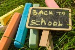 Mini blackboard pisać Z powrotem szkoła i kolorowa kreda na zielonej trawy tle fotografia stock