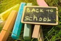 Mini blackboard pisa? Z powrotem szko?a i kolorowa kreda na zielonej trawy tle obrazy stock