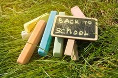 Mini blackboard pisa? Z powrotem szko?a i kolorowa kreda na zielonej trawy tle zdjęcia royalty free