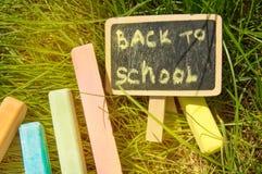 Mini blackboard pisa? Z powrotem szko?a i kolorowa kreda na zielonej trawy tle obraz stock