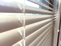 Mini blinds close-up. Aluminum white mini blinds, detail of cords going through holes in metal slats, window home interior window treatment covering, Venetian Stock Photo