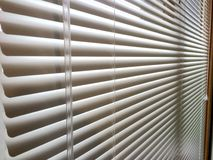 Mini blinds window wand. Aluminum white mini blinds with clear control wand, window home interior window treatment covering Venetian blinds Royalty Free Stock Photos