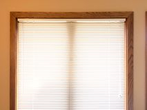 Mini blinds on wood window frame. Aluminum white mini blinds on a wood framed window, window home interior window treatment covering, Venetian blinds Royalty Free Stock Photos