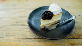 Mini blueberry cheesecake focused in black plate with fork on wooden table Royalty Free Stock Images