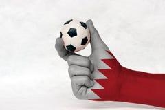 A mini bola do futebol na mão pintada bandeira de Barém, guarda-a com o dedo dois no fundo branco fotos de stock royalty free