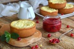 Mini bolo de queijo da airela em formulários do queque Servido na placa de corte com doce e bagas Copie o espaço Imagem de Stock