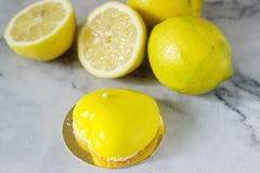 Mini bolo vitrificado do limão da musse decorado com grânulos e microplaquetas do coco foto de stock royalty free