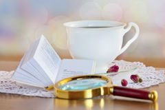 Mini book and magnifying glass on table Stock Image