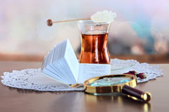 Mini book and magnifying glass on table Stock Photos