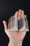 Mini book opened. A mini book on palm over black background royalty free stock photography