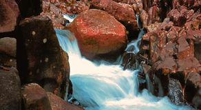 Mini bordadura bonita da paisagem da cachoeira pela rocha alaranjada na fotografia do movimento lento imagem de stock royalty free