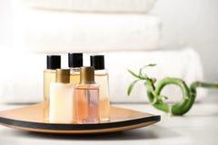 Mini botellas con los productos cosméticos y toallas en la tabla, espacio para el texto imágenes de archivo libres de regalías