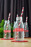 Mini bottle glass. Milk bottles and red striped paper straws for parties Stock Photography