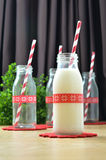 Mini bottle glass. Milk bottles and red striped paper straws for Parties Stock Image