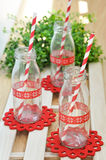 Mini bottle glass. Milk bottles and red striped paper straws for parties Royalty Free Stock Photo