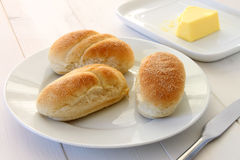 Mini Bread Rolls. Three fresh mini bread rolls with a dusting of polenta on a plate Royalty Free Stock Images