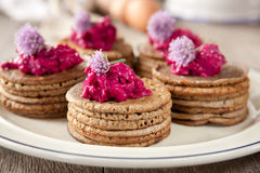 Mini buckwheat pancakes. Garnished with colorful beet salad and chives blossoms Stock Photo