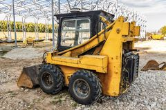 A mini excavator bulldozer is on the construction site. stock images