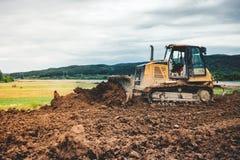 Mini- bulldozer som jämnar jordjord för huvudvägfundamentplats Arkivbild