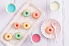 Mini bundt cakes. Iced mini bundt cakes with icing, a tray and a spoon Stock Photo
