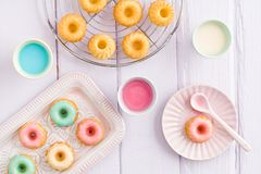 Mini bundt cakes. Iced mini bundt cakes with icing, a tray and a spoon royalty free stock images