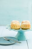 Mini bundt cakes. With icing sugar on a cake stand Stock Photo