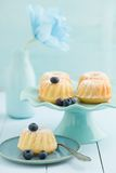 Mini bundt cakes. With icing sugar on a cake stand with blueberries and a paper flower stock image