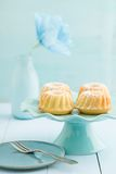 Mini bundt cakes. With icing sugar on a cake stand with a paper flower Royalty Free Stock Photos