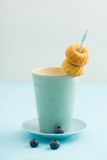 Mini bundt cakes. Put on a drinking straw into a cup of coffee with some blueberries royalty free stock images