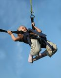 Mini Bungee Jumper. Smiling 4 year old blond girl on a mini bungee.  Isolated against blue sky Royalty Free Stock Image