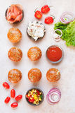 Mini burger buns topped with sesame seeds and various fillings Stock Photography