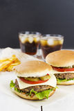 Mini burger with vegetables and meat, french fries and drink on a white wooden background.  Royalty Free Stock Photo