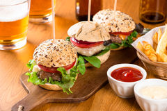 Mini burgers snack with fries and beer Stock Images