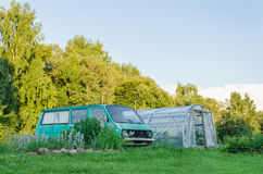Mini bus parked next to village greenhouse in yard Royalty Free Stock Photography