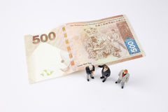 Mini business men on bank notes Stock Image