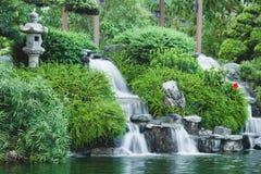 Mini cachoeira do estilo japonês com plantas verdes Projeto da paisagem Imagens de Stock Royalty Free