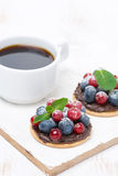 Mini cakes with chocolate cream and berries and a cup of coffee Royalty Free Stock Photo