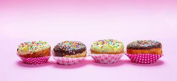 Mini cakes with icing and colorful sprinkles on pink background stock photos