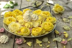 Mini Meringues of different colors and yellow roses Royalty Free Stock Photography