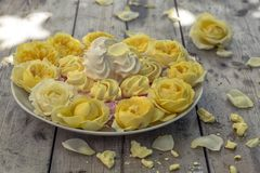 Mini Meringues of different colors and yellow roses Stock Image