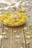 Mini Meringues of different colors and yellow roses Stock Photos