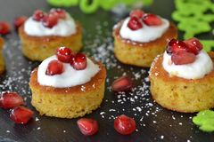 Mini cakes with pomegrenate. Mini orange cakes with yoghurt and pomegrenate Stock Photography