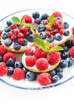 Mini cakes with sweet cream and berries on plate, vertical. Closeup Royalty Free Stock Photos