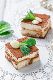 Mini cakes tiramisu with white chocolate, cocoa and candies on light background close up. Delicious dessert and candy bar Royalty Free Stock Photos