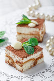 Mini cakes tiramisu with white chocolate, cocoa and candies on light background close up. Delicious dessert and candy bar. Stock Image