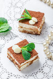 Mini cakes tiramisu with white chocolate, cocoa and candies on light background close up. Delicious dessert and candy bar. Royalty Free Stock Photos