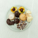 Mini cakes on a white plate on the festive table setting to cele Royalty Free Stock Image