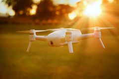 Mini Camera Drone Flying at Sunset Stock Photo