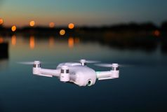 Small Camera Drone Flying (Evening Picture). Small size, portable camera drone, flying by a lake at a park after sunset stock image