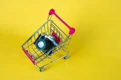 Mini camera toy and shopping cart or supermarket trolley on yell. Ow background with copy space for add text Royalty Free Stock Photo